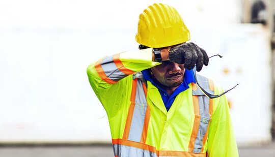 एक निर्माण श्रमिक गर्मी में अपना माथा पोंछता है