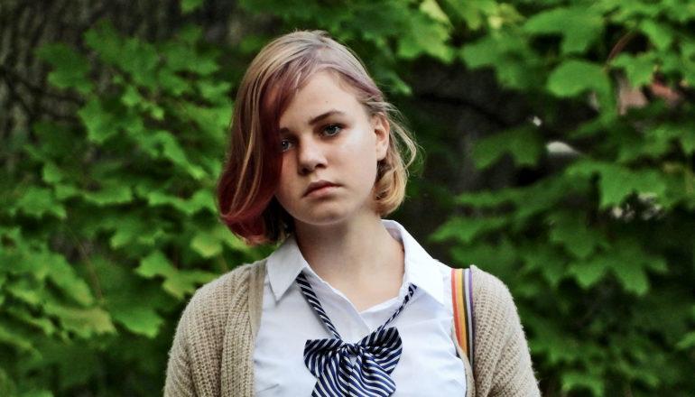 adolescente com franja tingida de rosa parecendo triste ao ar livre