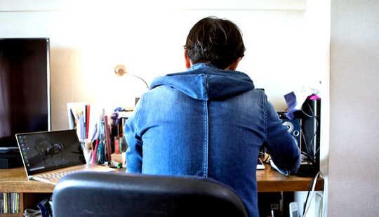baksiden av personen som sitter ved skrivebordet
