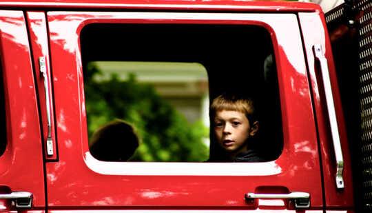 빨간 트럭의 확장 된 택시 창에 아이의 얼굴