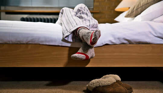 Benene til en person henger over siden av sengen