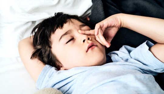 En ung pojke gnuggar i ögat när han ligger i sängen