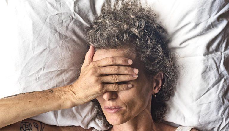 Μια γυναίκα που ξαπλώνει σε ένα άσπρο μαξιλάρι βάζει το χέρι της πάνω από το πρόσωπό της