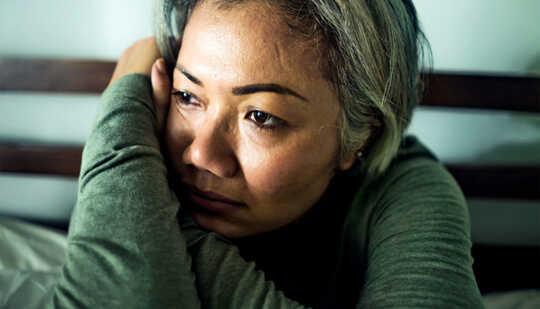 Una donna seduta a letto si appoggia sulle braccia