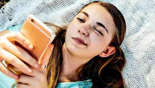 Seorang remaja membaca teleponnya dengan ekspresi bingung di wajahnya