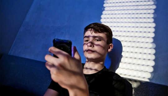一個十幾歲的男孩坐在床上看手機