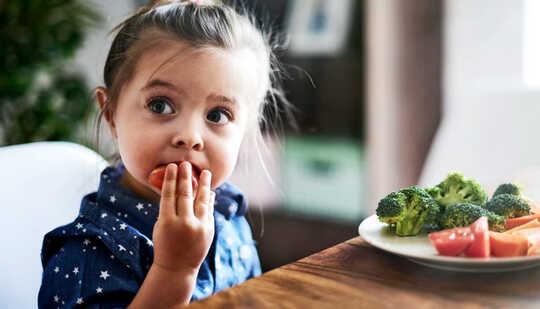 Ένα μικρό κορίτσι τρώει λαχανικά από ένα πιάτο καθμένος σε ένα τραπέζι