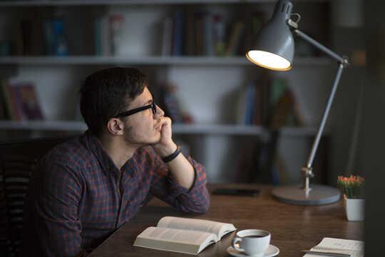 Mann mit Buch schaut in die Ferne