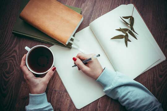 persona che scrive su un quaderno con in mano una tazza di caffè