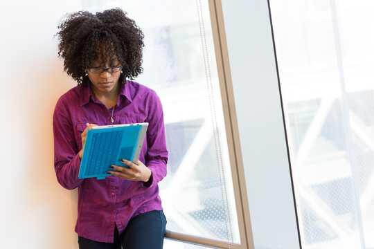 Seorang wanita di pejabat meneliti dokumen.