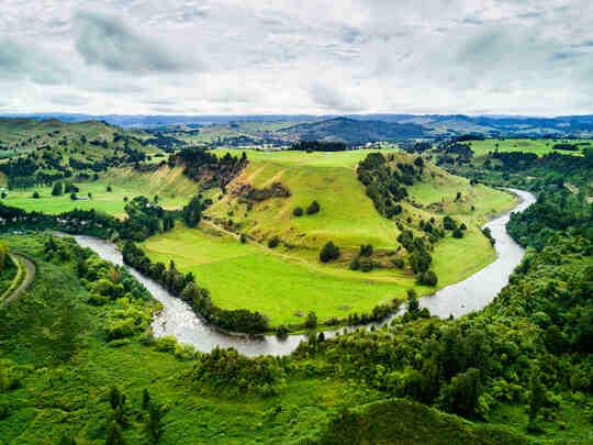 Sebuah sungai yang berkelok-kelok melalui lembah hijau yang subur