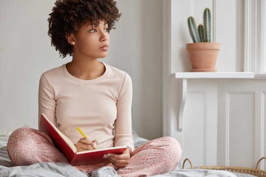 La donna si ferma a guardare fuori dalla finestra mentre scrive su un quaderno.