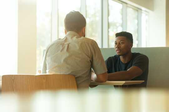 zwei sitzende Männer im Gespräch