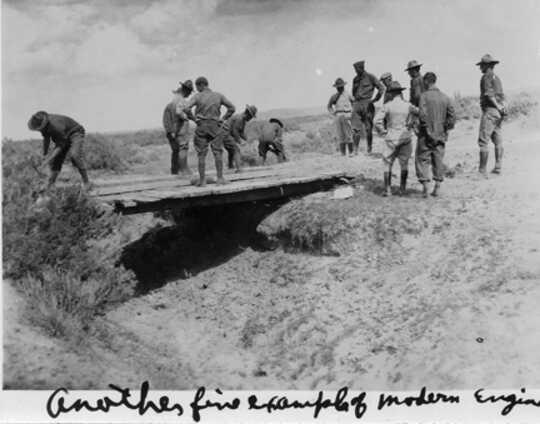 يقوم الجنود بتقييم جسر خشبي فوق أخدود.