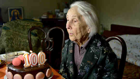 100-vuotias nainen puhaltaa syntymäpäiväkakun kynttilät.