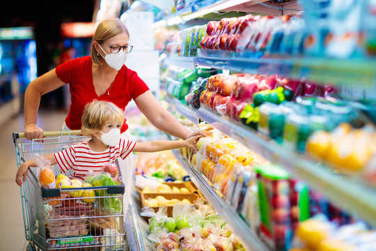 母亲和孩子在超市购买蔬菜。