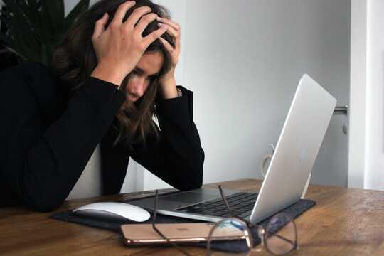Seorang wanita dengan kepalanya di tangan di hadapan komputer riba