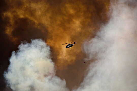 Helikopter kelihatan di asap api liar.