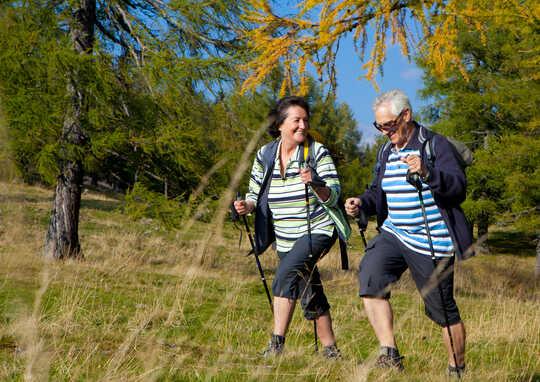 Et eldre par bruker trekkingstokker mens de går på tur.