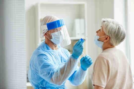 Медицинский работник проводит мазок на COVID у пациента.