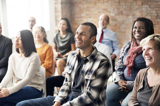 En gruppe voksne i klasserom, smiler til læreren som er utenfor rammen.