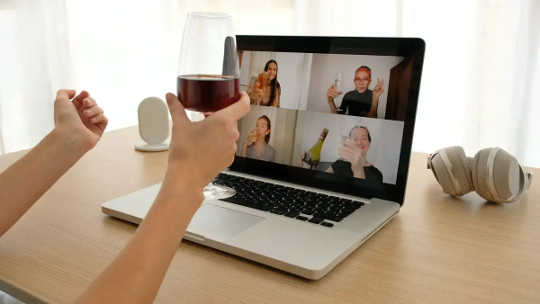 婦女喝在顯示錄影電話的膝上型計算機前面的酒。