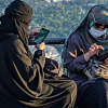 two Muslim women wearing the niqab and using their cell phones