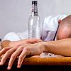 男人在一張桌子上昏倒,手裡拿著一瓶空酒,孩子在旁邊看著