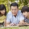兩個孩子和父親一起看書