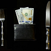 a table setting with a knife and fork and a wallet full of money where the plate usually would be