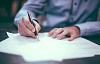 gambar seorang pria yang sedang menulis di atas kertas