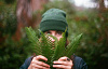 a young man holding some ferns and using them to hide behind