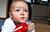 Un bébé sur le sol lève les yeux avec un front plissé