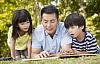 hai đứa trẻ đọc sách với cha của chúng