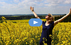 woman standing in a field of flowers with arms upstretched to the sun