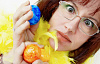 image of woman holding up two colored eggs... with a surprised look on her face