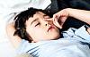 Ein kleiner Junge reibt sich die Augen, während er im Bett liegt