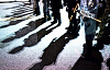 Eine Polizeilinie mit Schutzschildern auf der Straße wirft Schatten auf den Asphalt