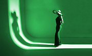 a model standing on a runway facing her shadow... all in green