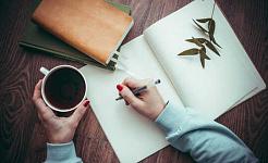 orang yang menulis di buku nota yang memegang secawan kopi