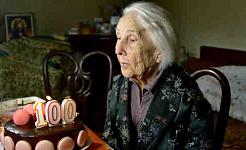 100-летняя женщина задувает свечи на своем праздничном торте.