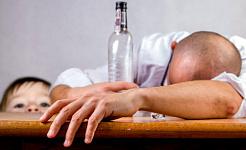 El hombre se desmayó en una mesa con una botella vacía de alcohol con el niño mirando