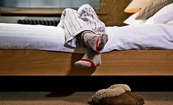 एक व्यक्ति के पैर उनके बिस्तर के किनारे लटक जाते हैं