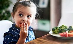 En liten jente spiser grønnsaker fra en tallerken mens hun sitter ved et bord
