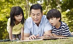 dua anak membaca buku bersama ayah mereka