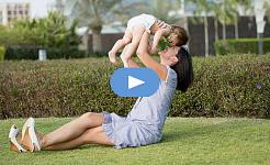 leende mamma, sitter på gräset, håller upp ett barn