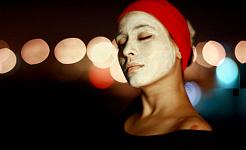 زنی که عمامه به سر دارد و روی صورتش ماسک گلی یا گلی است