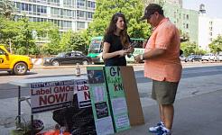 امرأة من مجموعة أبحاث المصلحة العامة في نيويورك تتحدث إلى أحد المارة عن المخاطر المحتملة للكائنات المعدلة وراثيا أمام سوق Whole Foods في نيويورك في يونيو 3 ، 2014. (جوناثان تشو / Epoch Times)