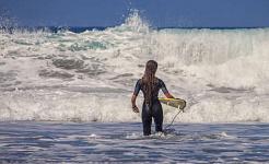 серфер с крошечной доской для серфинга на огромных волнах