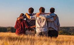 4 adultos jóvenes sentados juntos con los brazos entrelazados sobre los hombros, vistos desde atrás